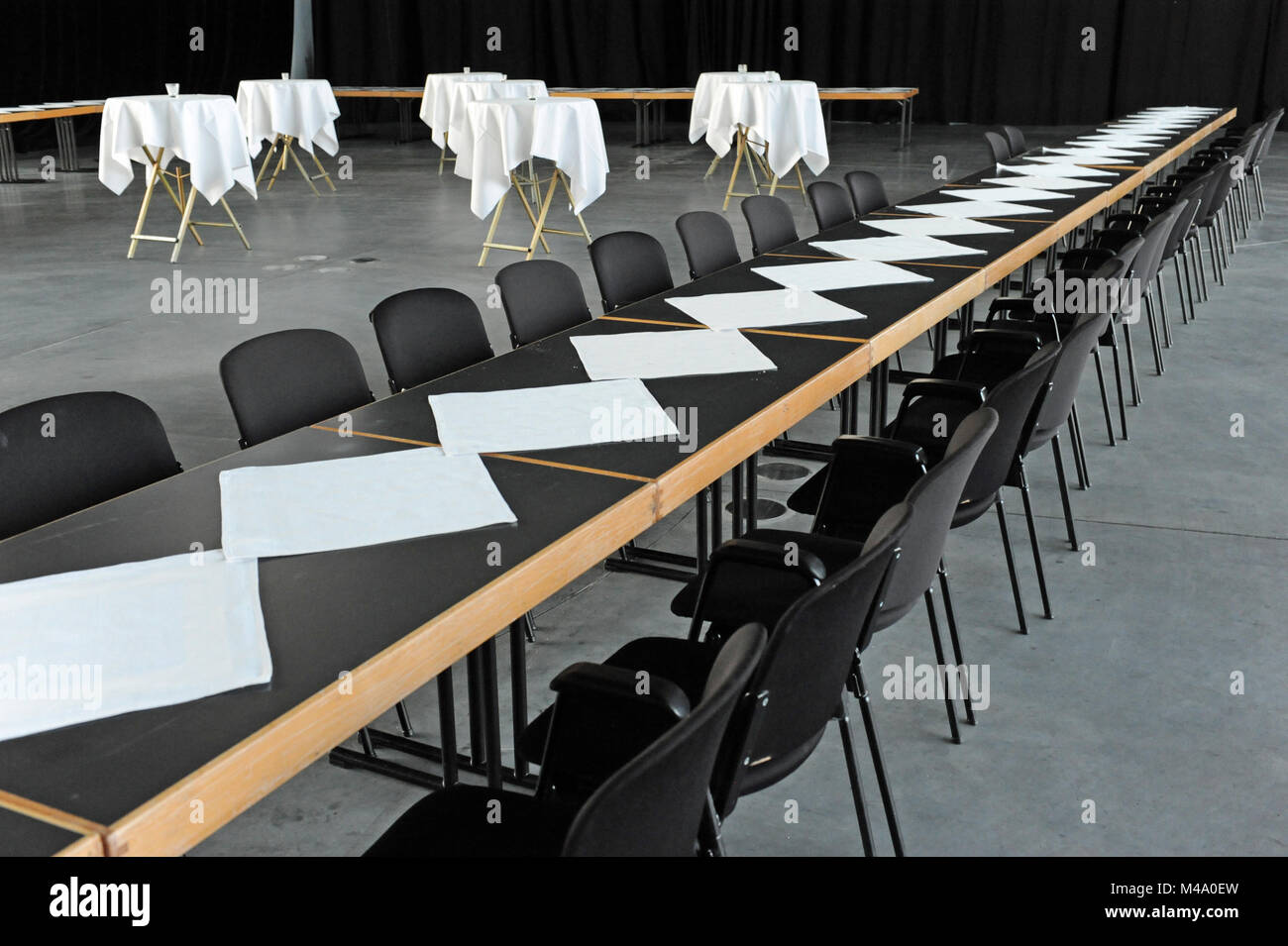 round tables with white tablecloths in a room - Stock Image