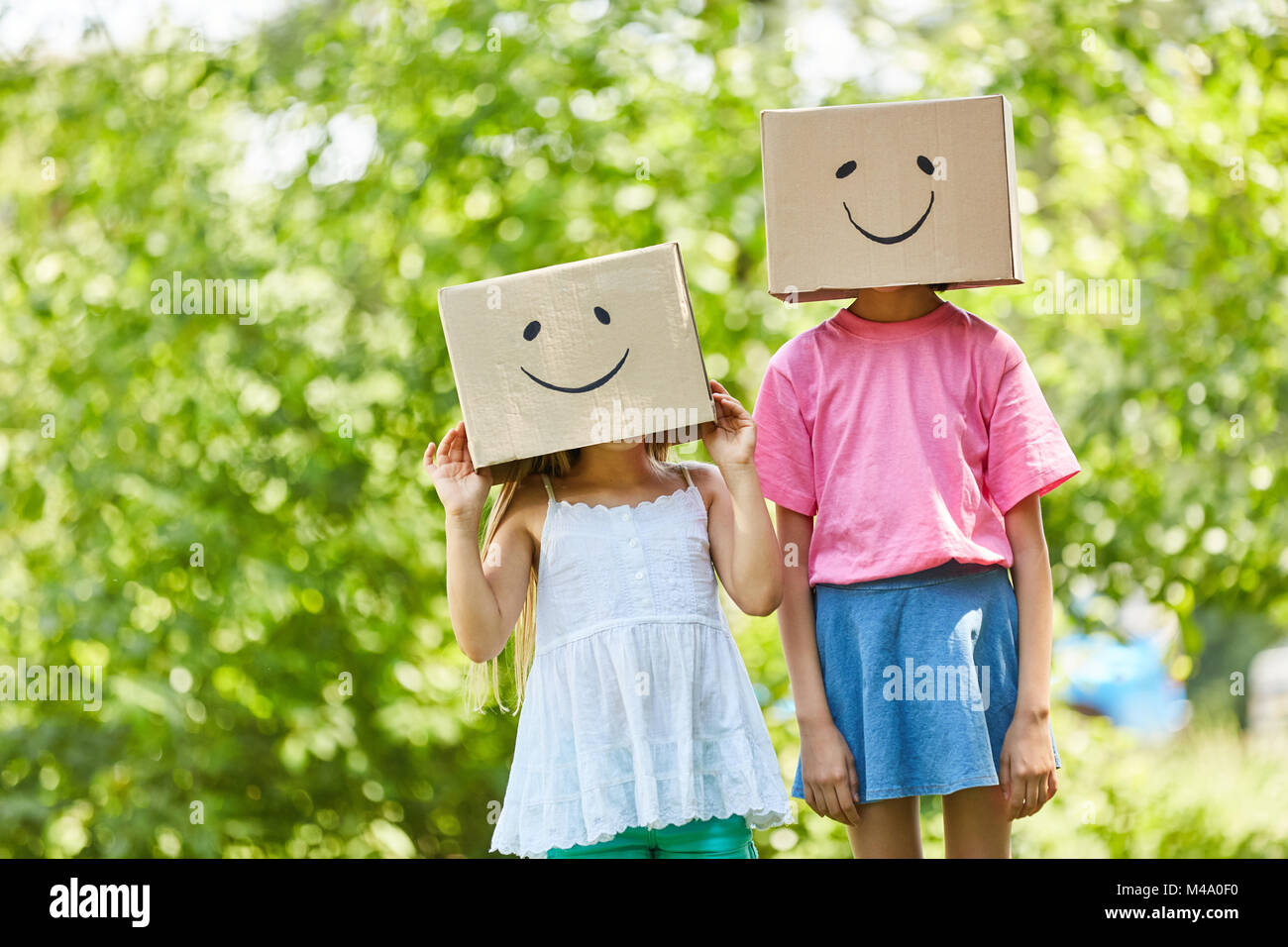 Two children hide their faces under funny painted cardboard boxes - Stock Image