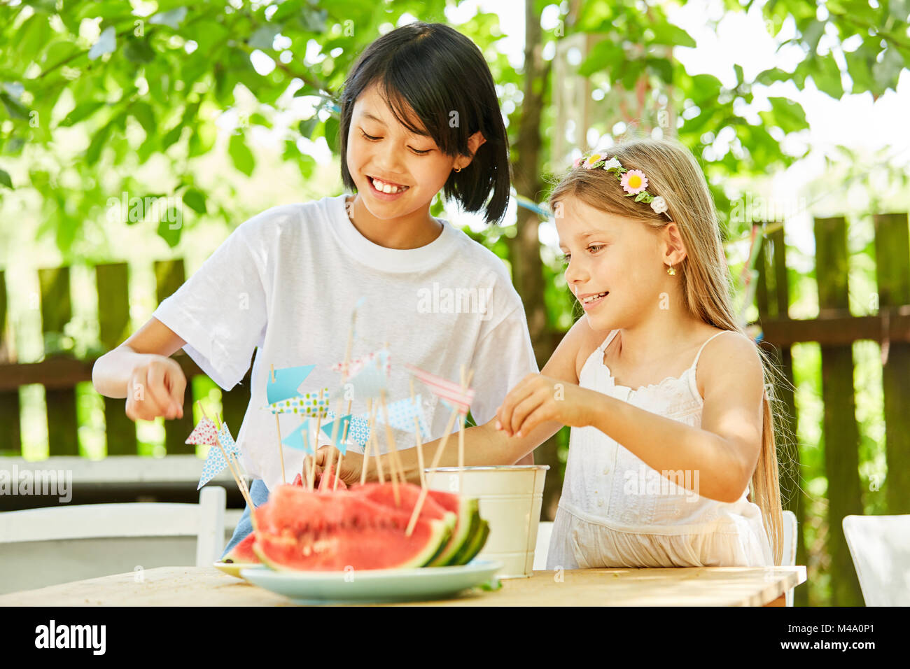 Two girls as friends decorate watermelons with little flags - Stock Image