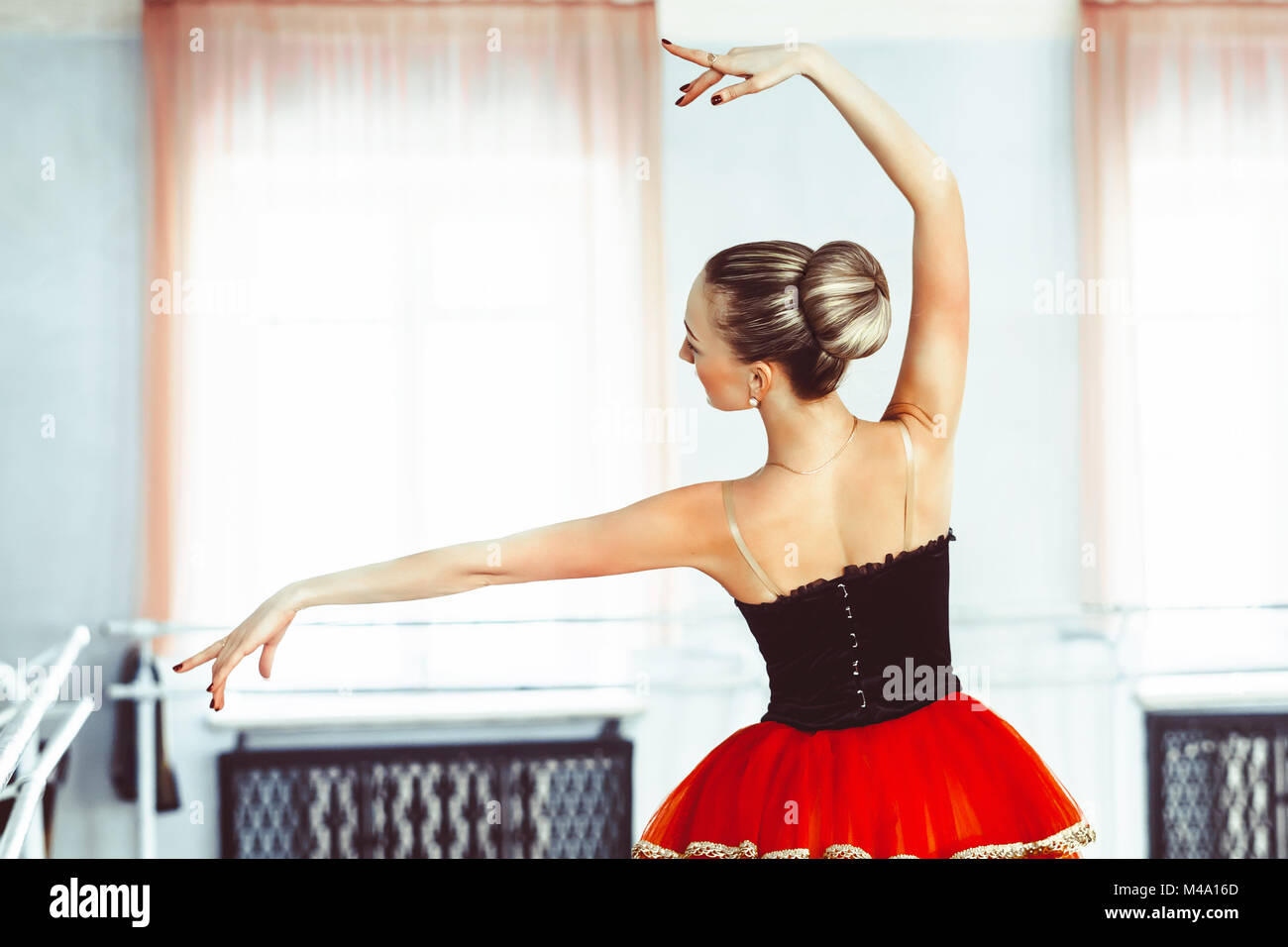 Classical Ballet dancer side view. Beautiful graceful ballerine practice ballet positions in tutu skirt near large - Stock Image