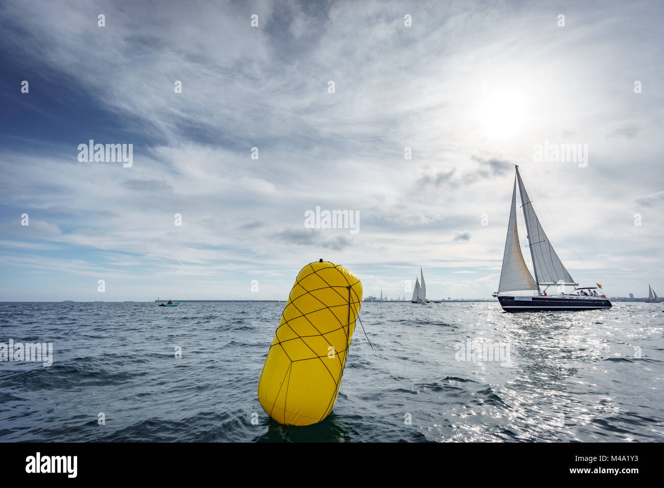 Buoy and sailing boat in the sea - Stock Image