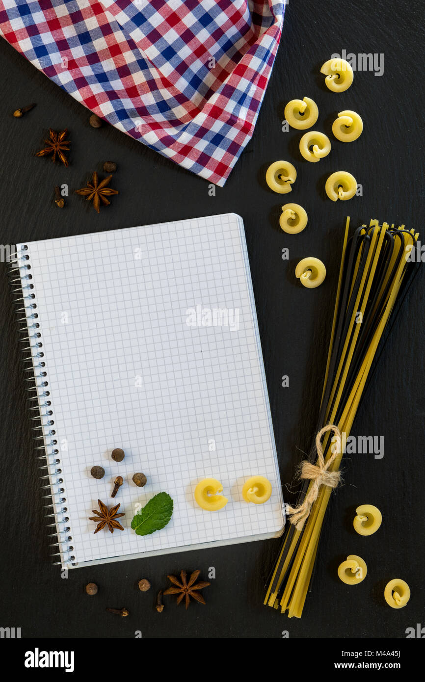 Blank cookbook with conventional and black uncooked Italian pasta - Stock Image