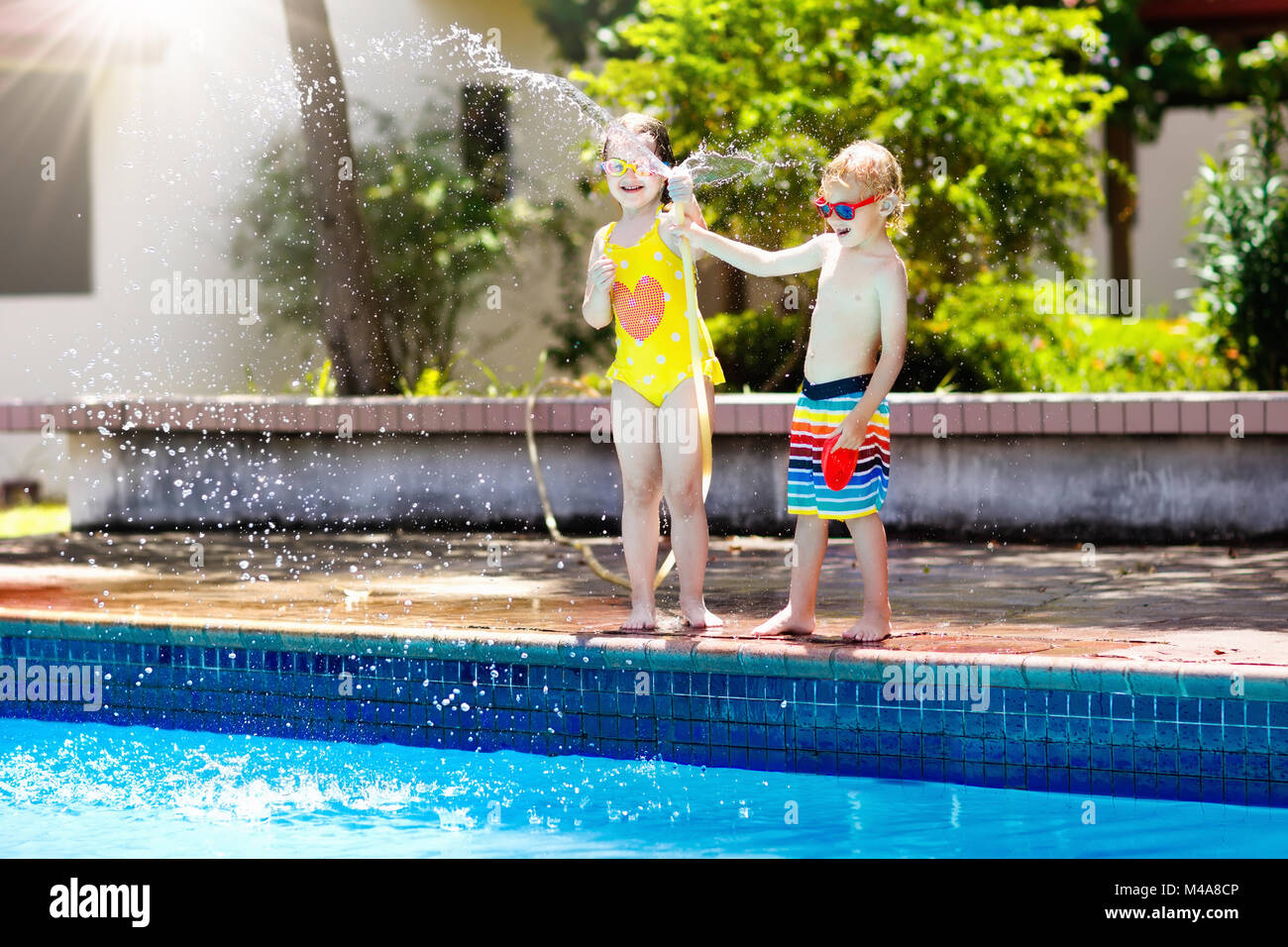 Kids playing with garden hose in backyard with large outdoor ...