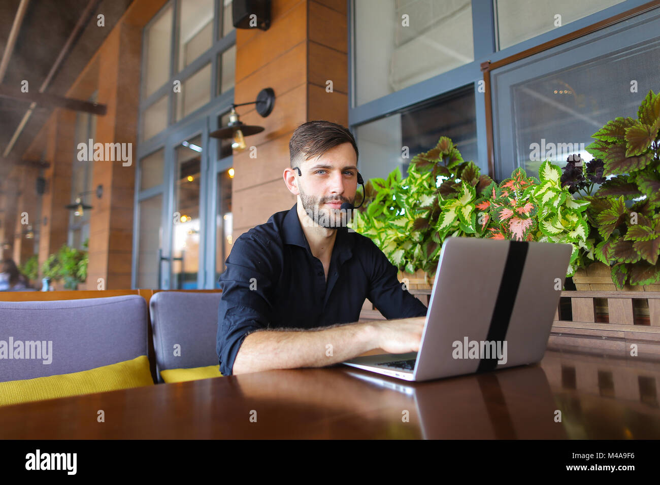 Internet consultant talking to client with web camera and microp - Stock Image