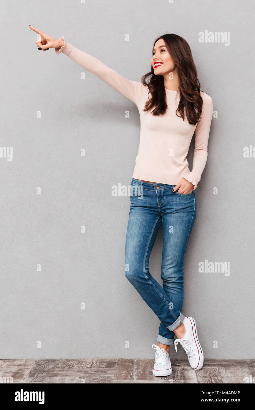 Full-length image of positive adult girl with brown hair pointing index finger aside showing or paying attention - Stock Image