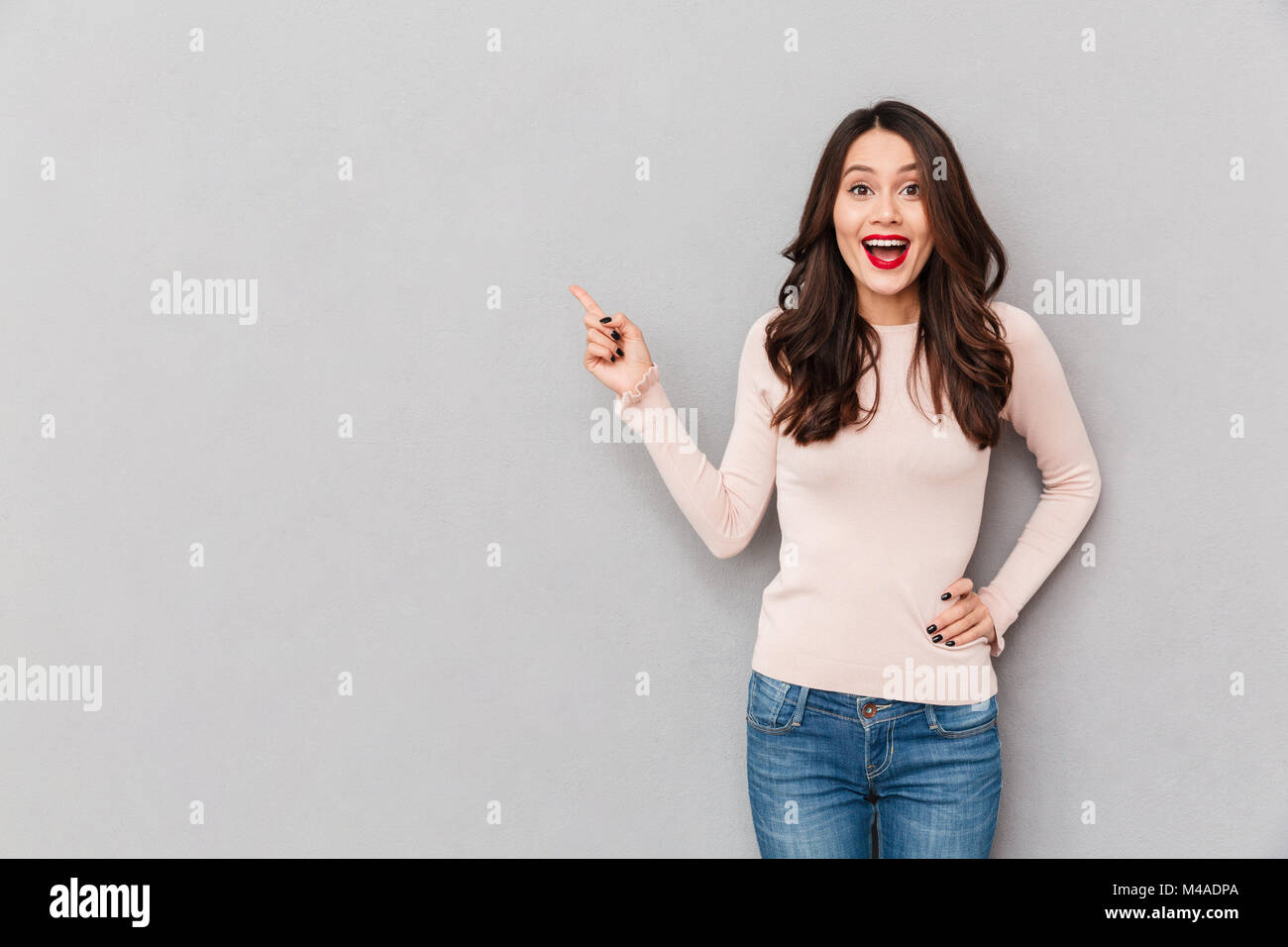 Image of pretty excited girl with brown hair pointing index finger aside showing or paying attention on something, - Stock Image