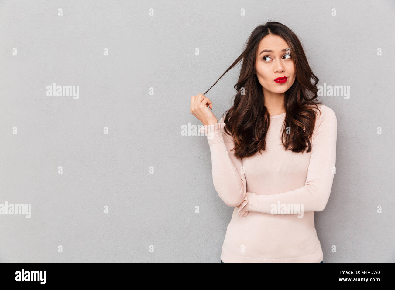 Portrait of young tricky woman touching lock of hair meaning she has something in mind with facial expressions, - Stock Image