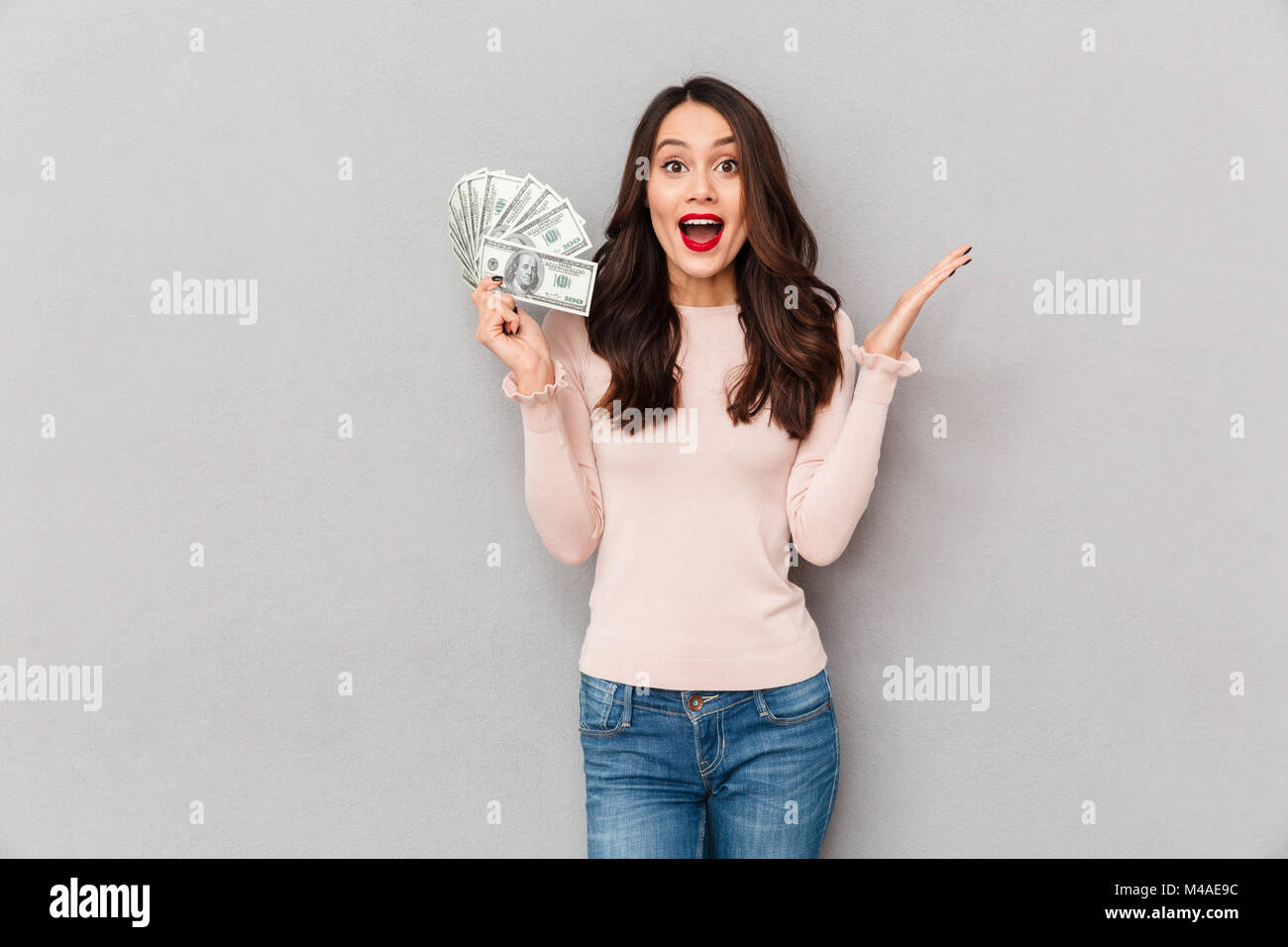 Image of gorgeous brunette female model with long hair and red lips holding fan of 100 dollar bills, being rich - Stock Image