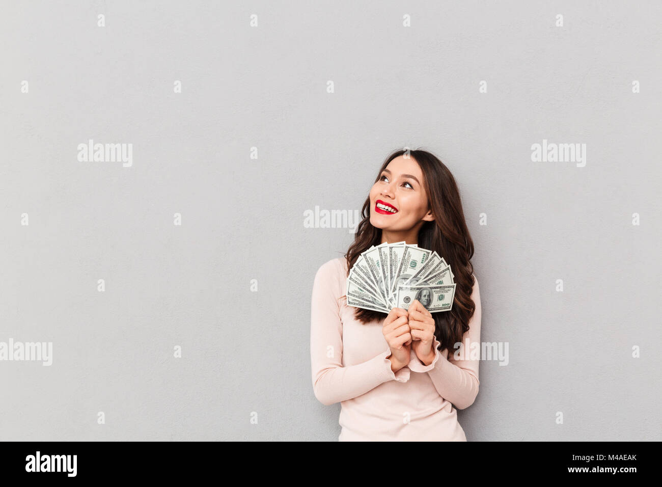 Successful brunette adult girl holding fan of 100 dollar bills being rich and happy looking aside, over gray wall - Stock Image