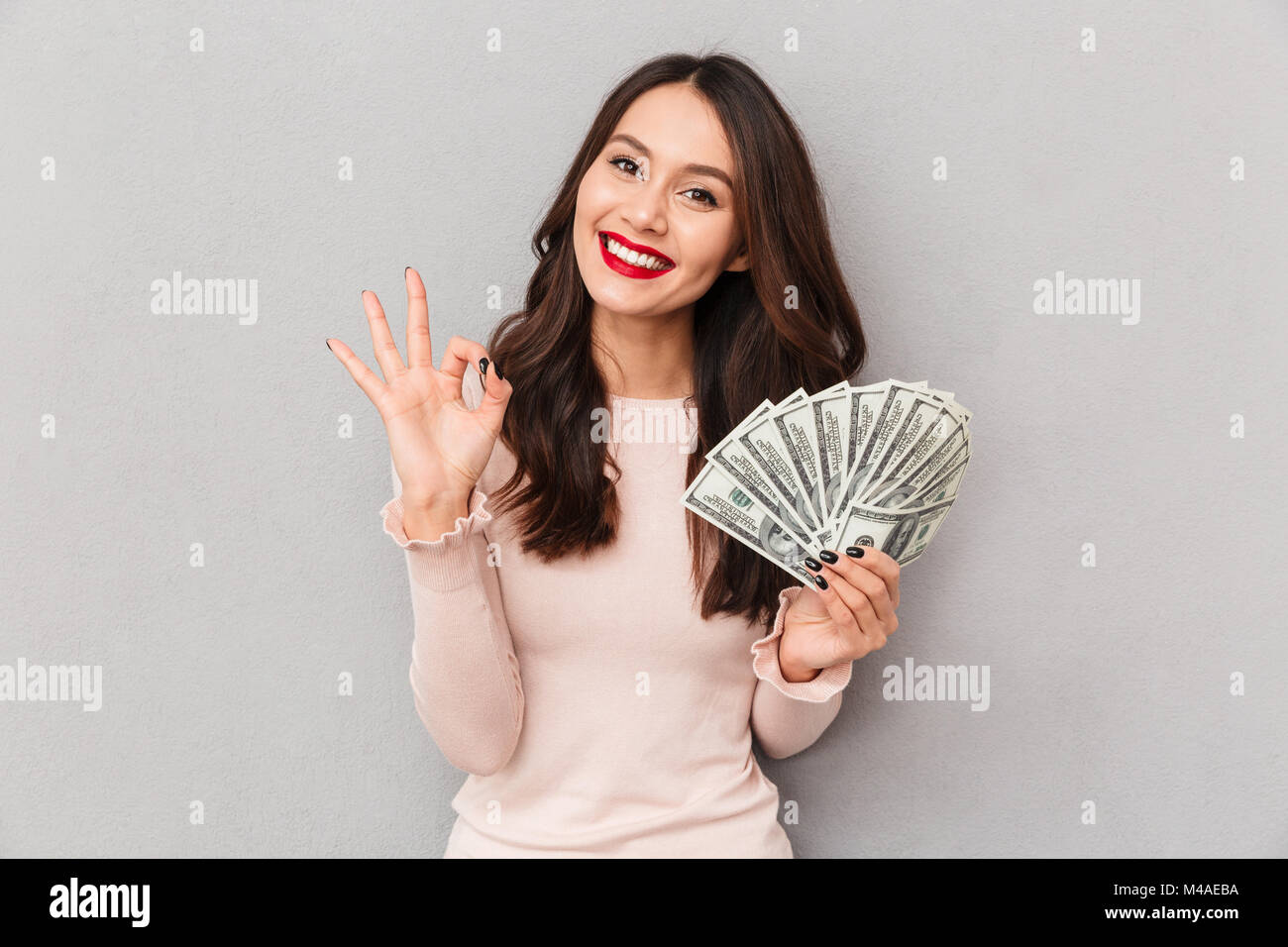 Image of lucky brunette female holding fan of 100 dollar bills being excited to win cash prize showing OK sign, - Stock Image