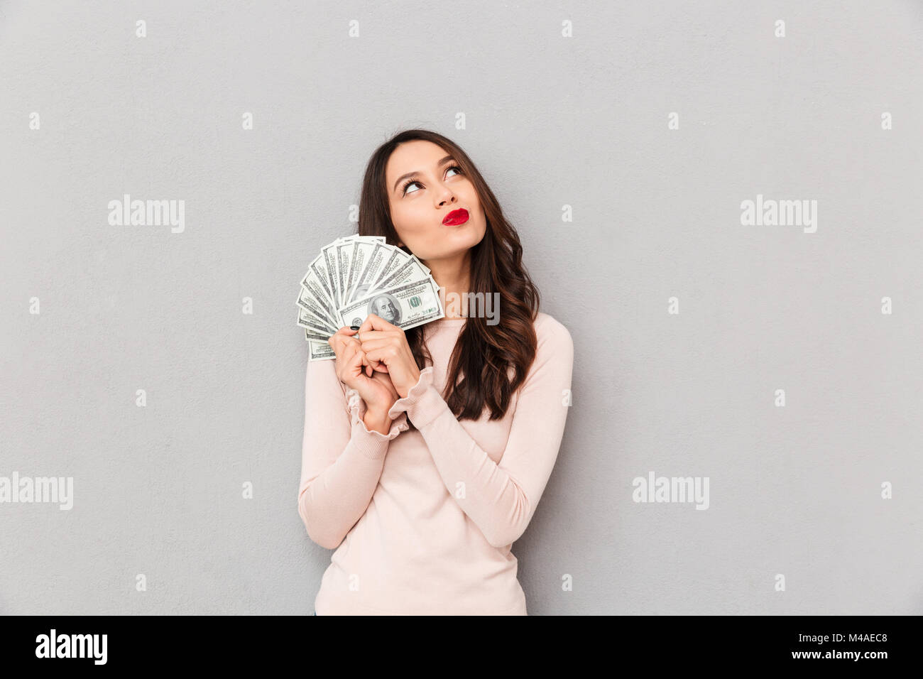 Image of lucky brunette female holding fan of 100 dollar bills being excited to win cash prize, expressing victory - Stock Image