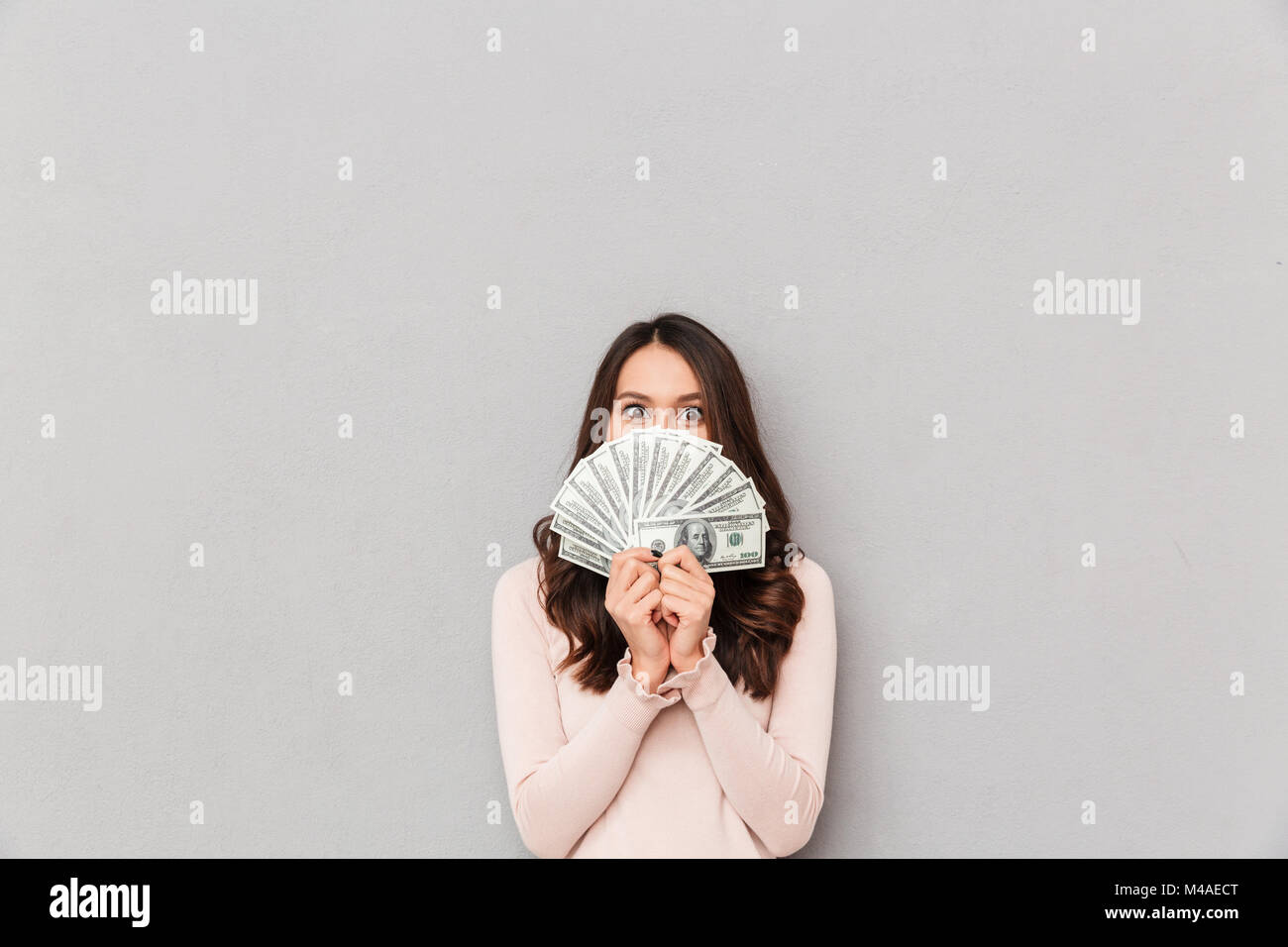 Image of lucky happy woman covering her face with fan of 100 dollar bills, having lots of cash money over gray wall - Stock Image