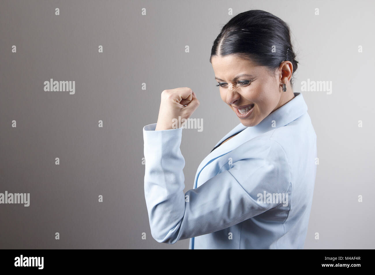 Victorious and successful young businesswoman - Stock Image