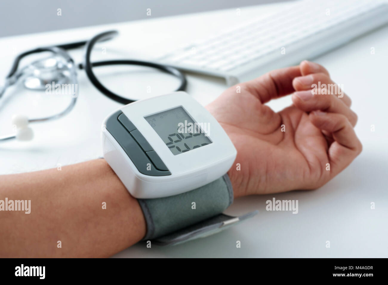 closeup of the arm of a caucaisan patient man whom is being measured his blood pressure with a sphygmomanometer - Stock Image