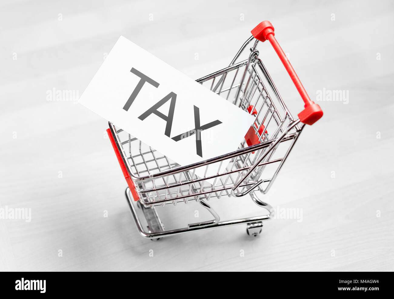 Tax, taxation and VAT concept. Shopping cart with a card or paper sign. - Stock Image
