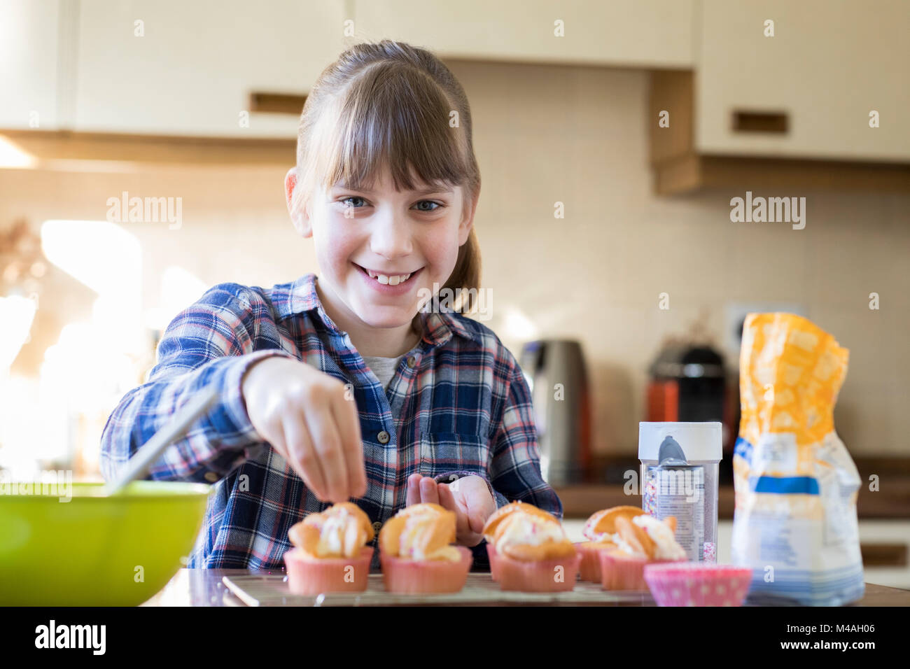 Portrait Of Girl In Kitchen Decorating Home Made Cupcakes - Stock Image