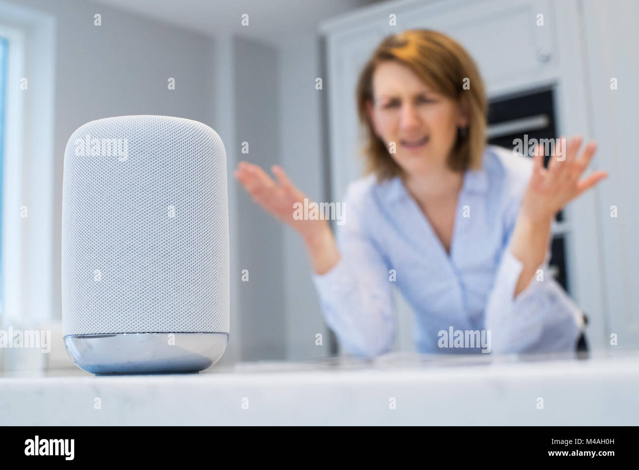 Frustrated Woman In Kitchen Asking Digital Assistant Question Stock Photo