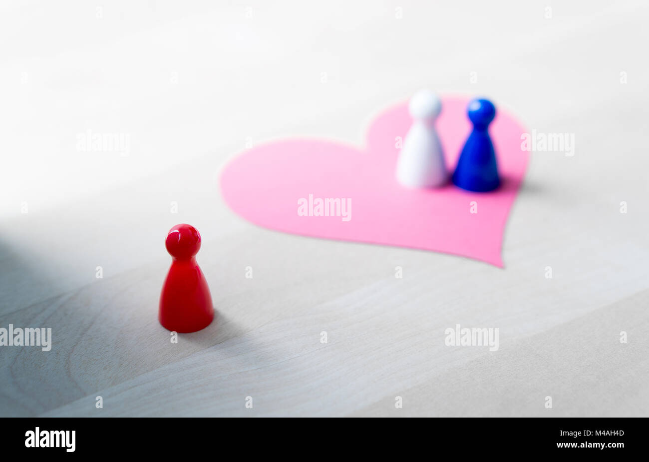 Having affair, infidelity or cheating concept. Love triangle or being third wheel. Board game pawns and paper heart - Stock Image