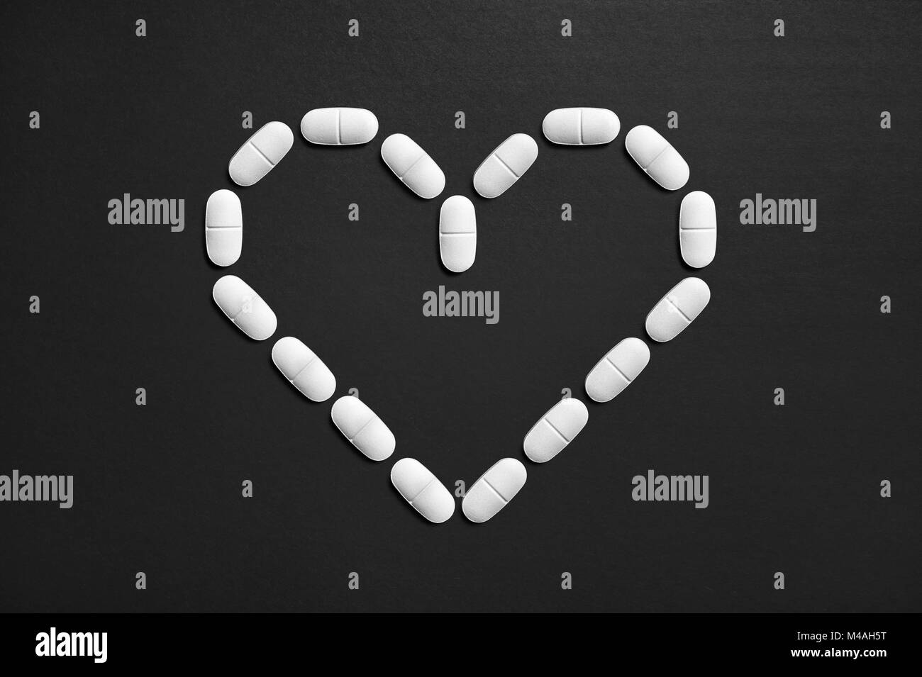 Love symbol made from pills. Heart attack and disease concept. High or low blood pressure medicine. Loving and nurturing - Stock Image