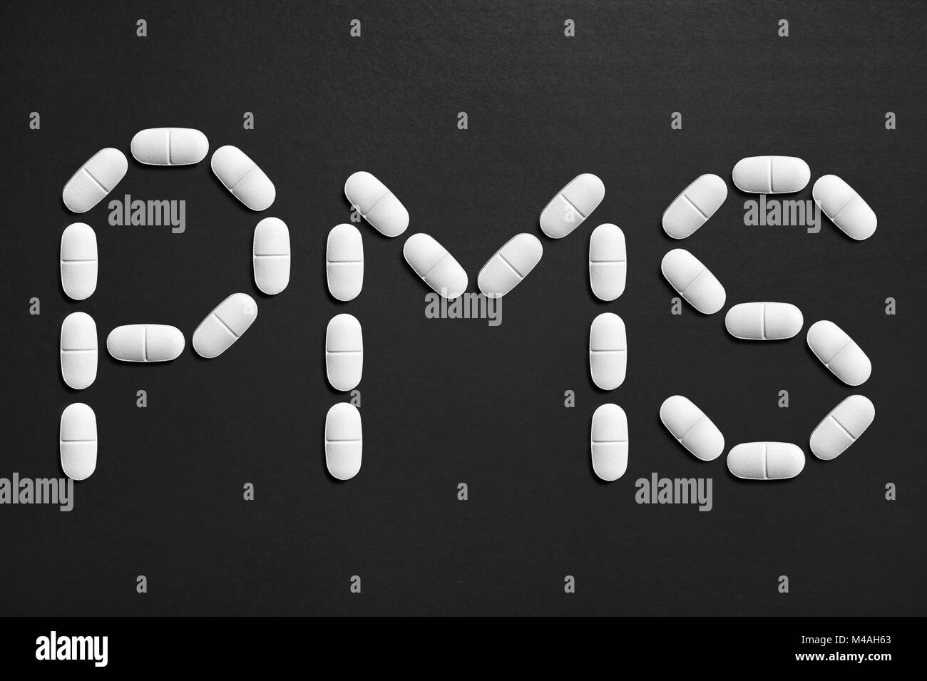 PMS text made from pills. Menstruation and having period concept. Stock Photo