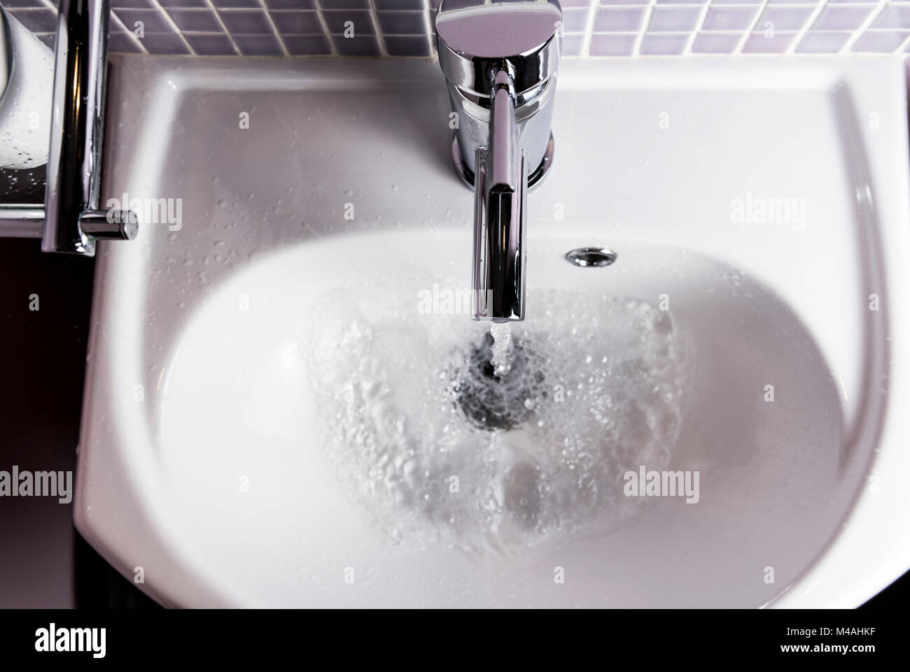 Water running from a bathroom tap or faucet, into a a hand basin. - Stock Image