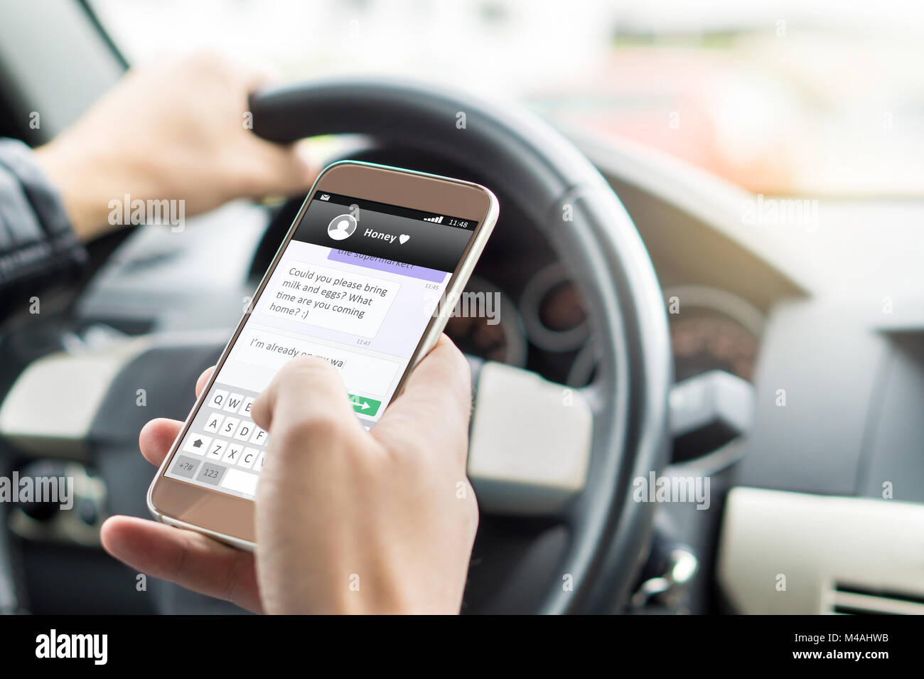 Texting while driving car. Irresponsible man sending sms and using smartphone. Writing and typing message with cellphone - Stock Image