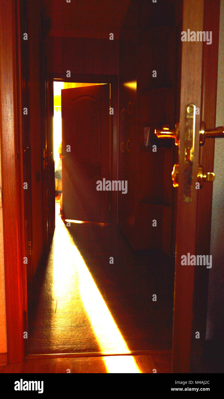 A beam of light falling on the floor through the open door in the room - Stock Image