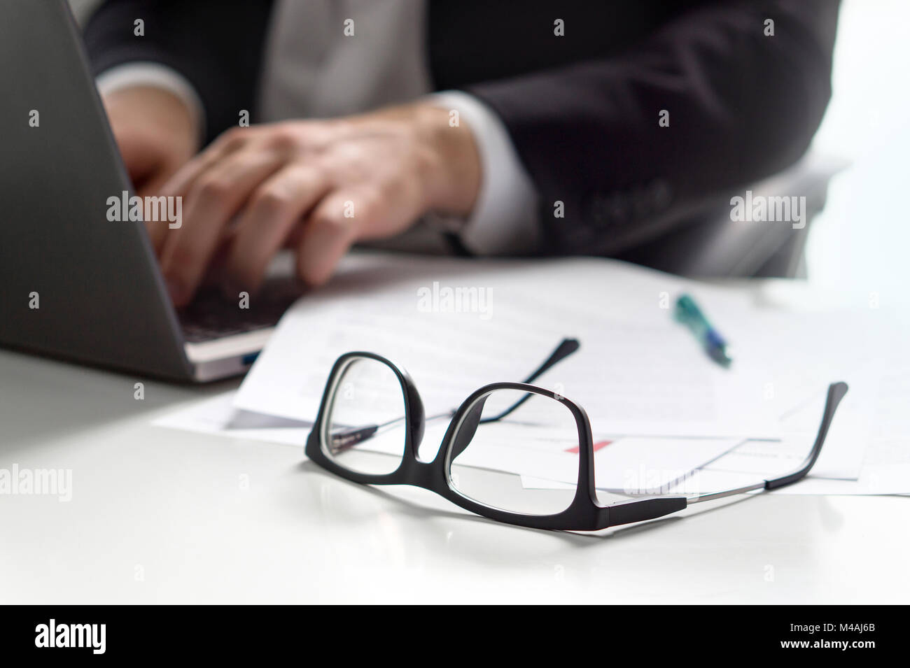 Business man writing with laptop in office with glasses on table. - Stock Image