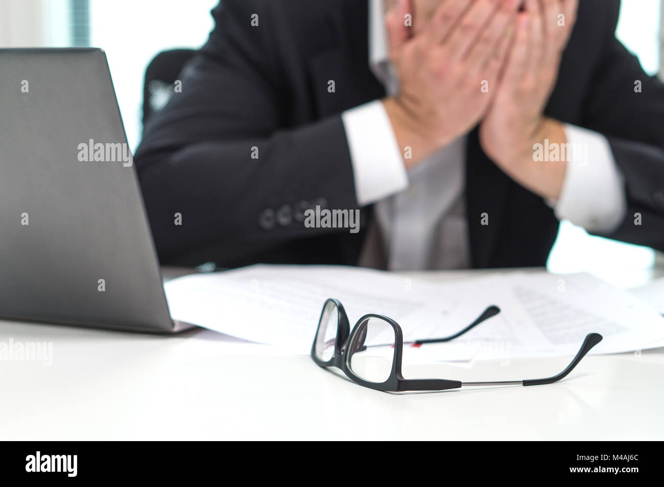 Stressed business man covering face with hands in office. Working over time or too much. Problem with failing business - Stock Image