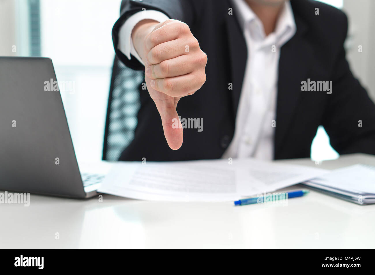Business man showing thumbs down in office. - Stock Image