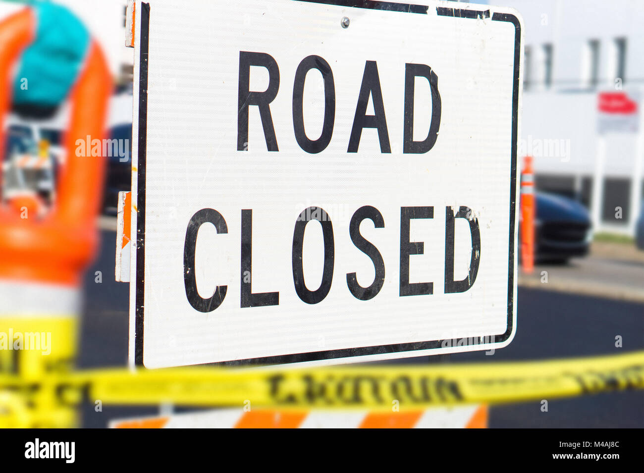 Road closed sign and block in a busy city street in the middle of traffic. Roadblock in a highway. - Stock Image