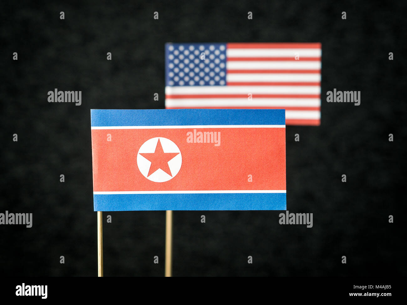 The flag of North Korea and United States of America (USA) made from paper on wooden stick against dark background. - Stock Image