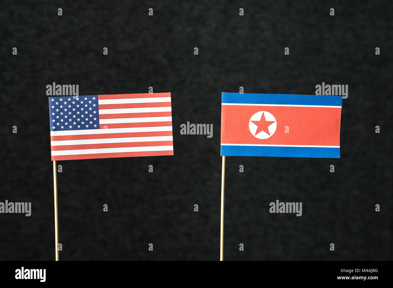 The flag of United States of America (USA) and North Korea made from paper on wooden stick against dark background. - Stock Image