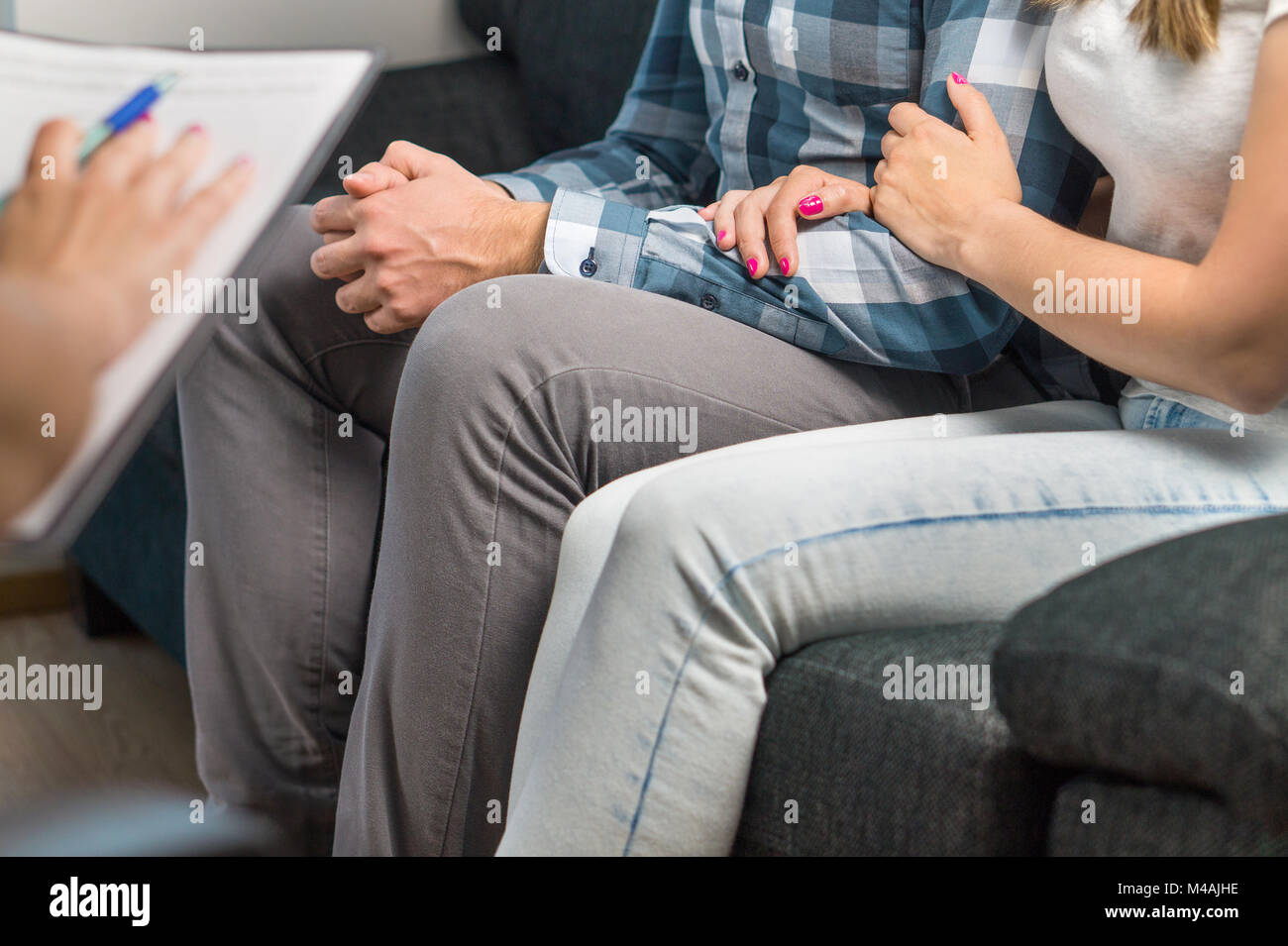 Couples therapy or marriage counseling. Woman hugging man's hand on couch during a psychotherapy session. Psychologist, - Stock Image