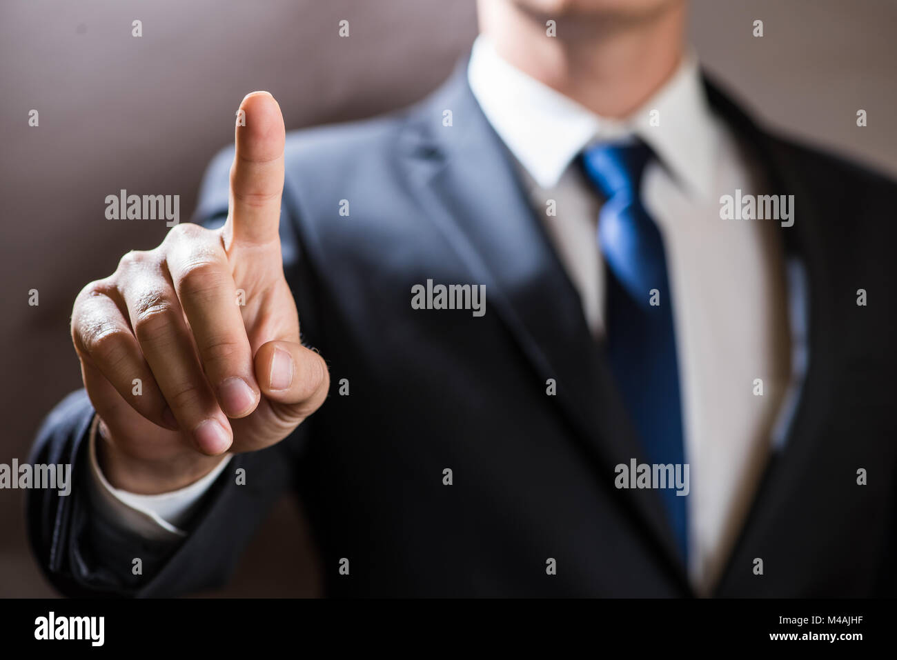 Businessman click on virtual touchscreen. Futuristic IT presentation background - Stock Image