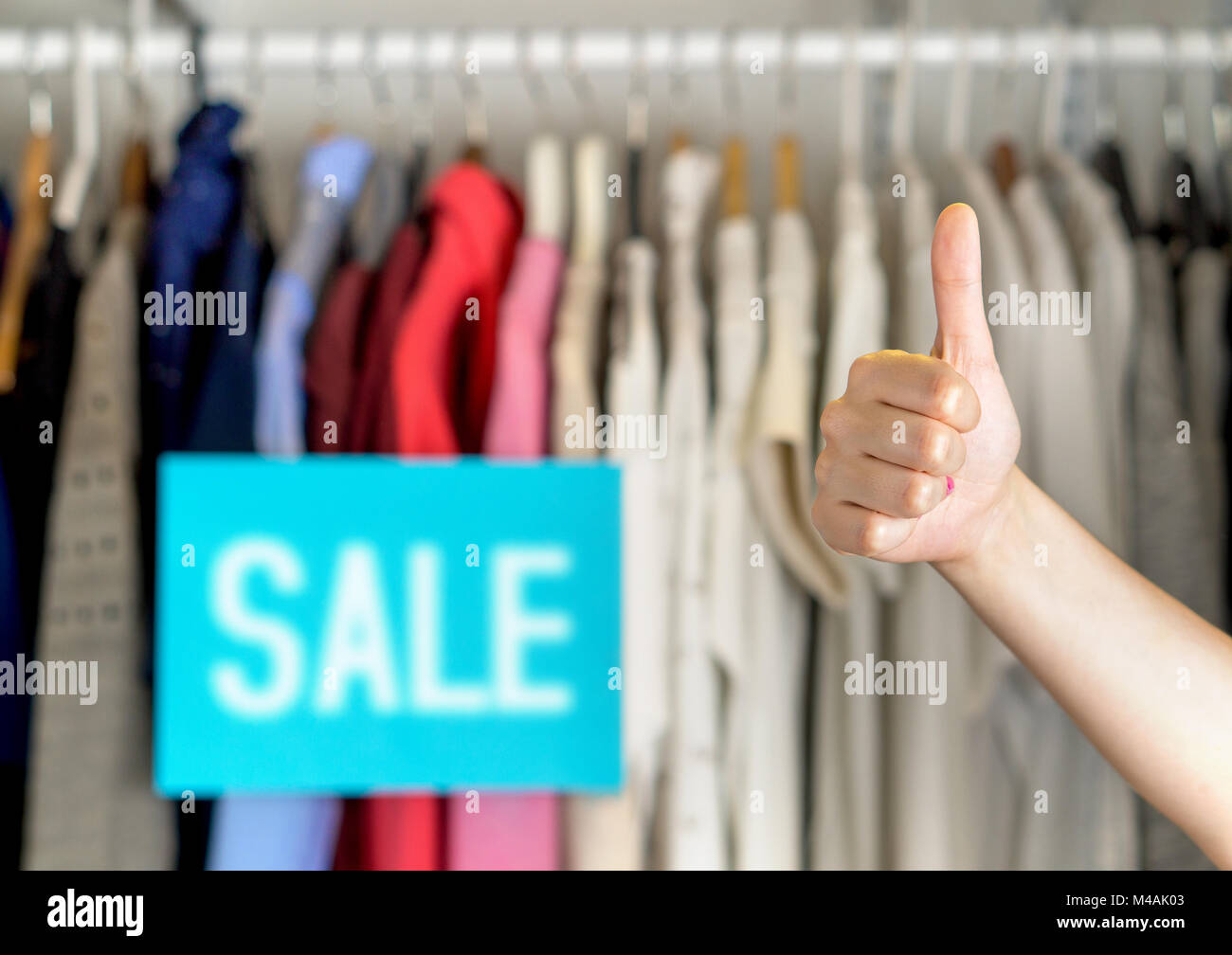 Happy and satisfied customer giving thumbs up in a clothing store for good service or great product quality. - Stock Image