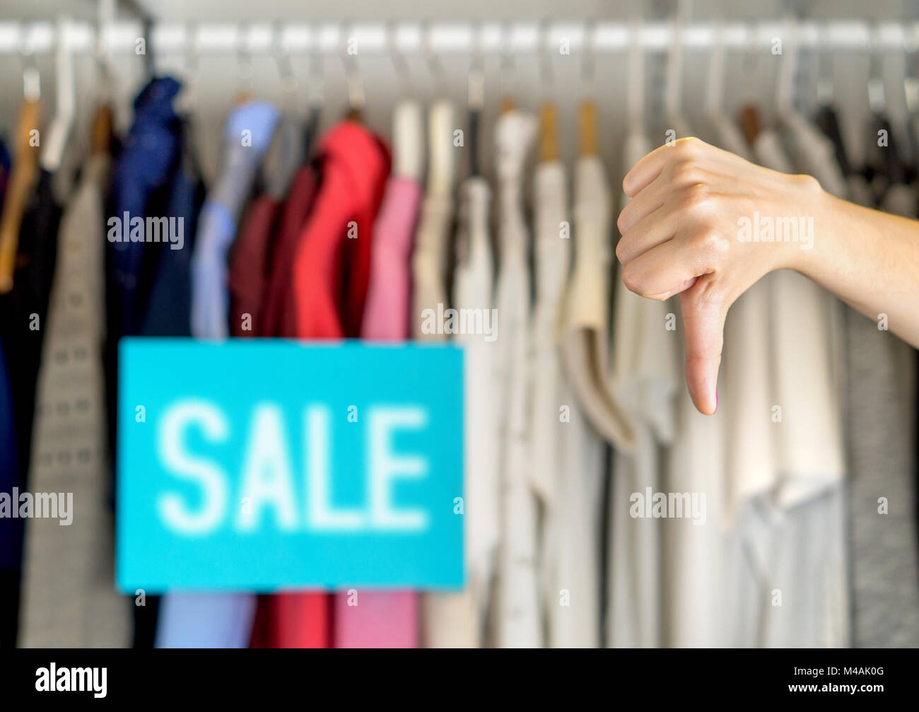 Unhappy and dissatisfied customer giving thumbs down in a clothing store for bad service or product quality. - Stock Image