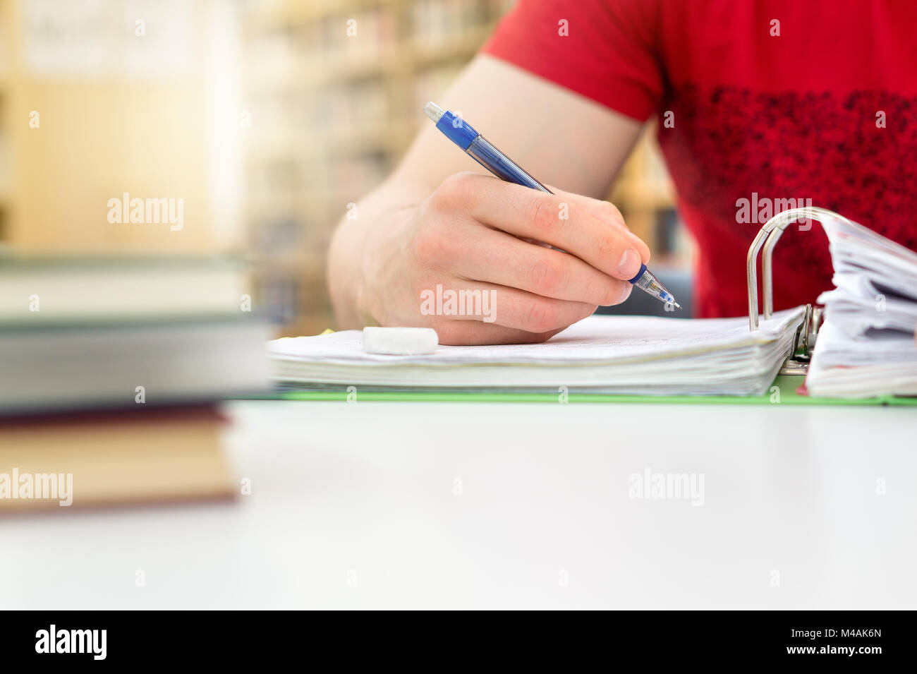 Young athletic man and student studying and writing notes in public or school library in college or university. - Stock Image