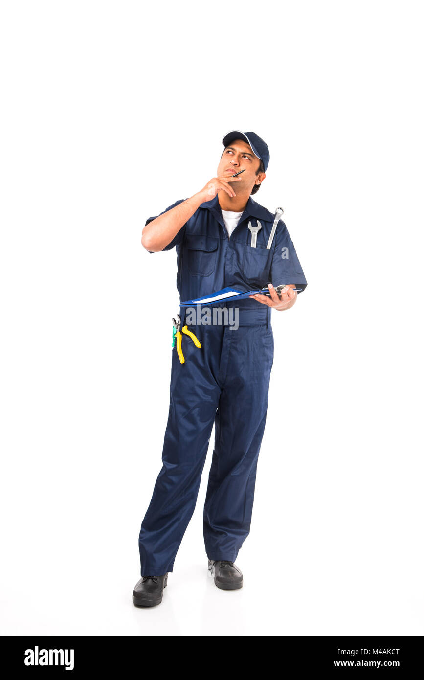 Indian happy auto mechanic in blue suit and cap holding spanner tool in action, isolated over white background - Stock Image