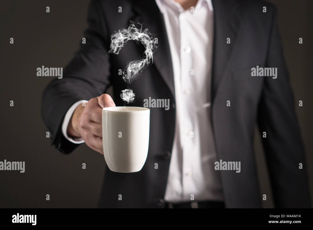Question mark from coffee steam. Smoke forming a symbol. Business man in a suit holding a hot beverage in a mug - Stock Image