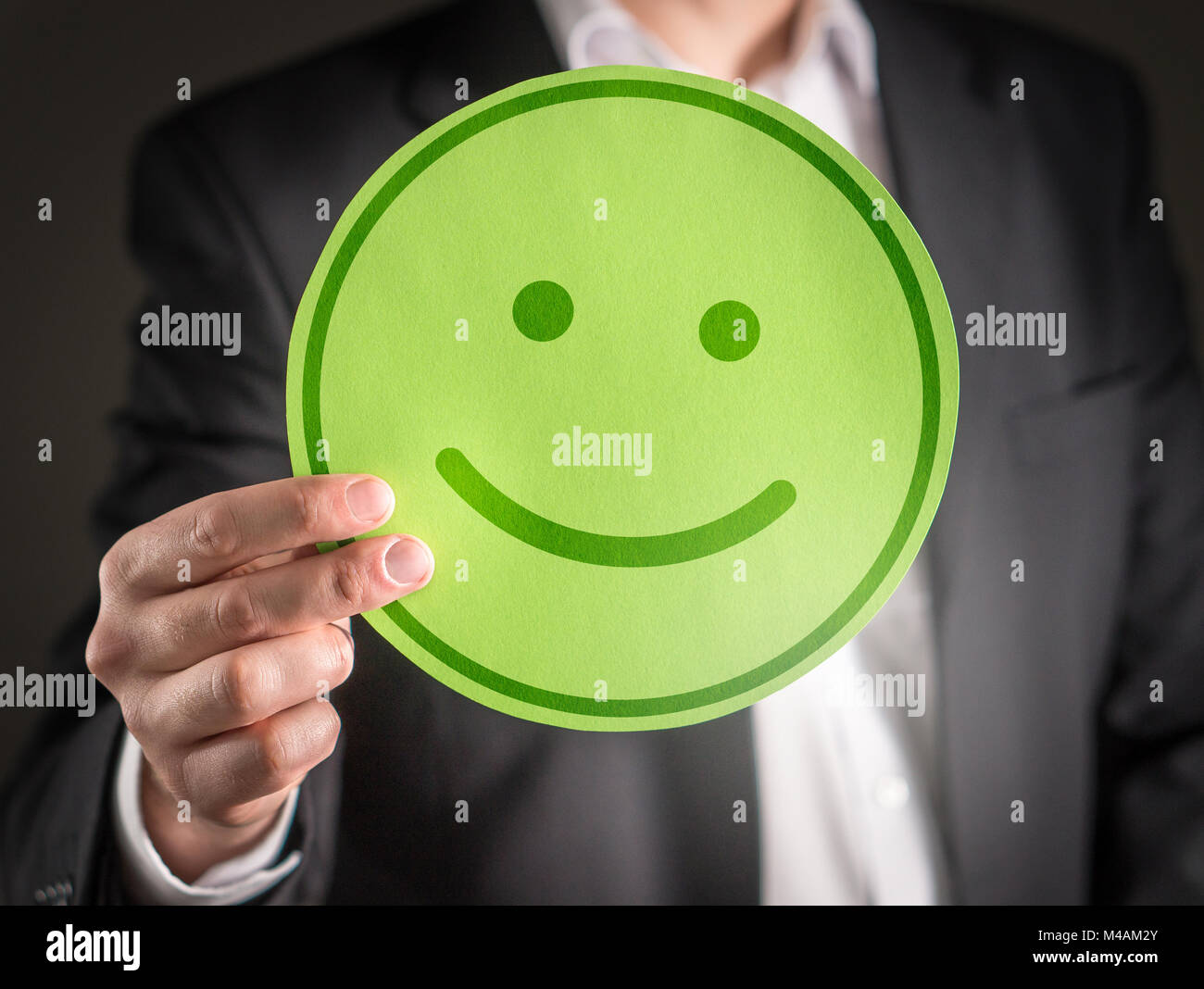Business man with happy cardboard smiley face emoticon. Customer satisfaction or successful business concept. - Stock Image