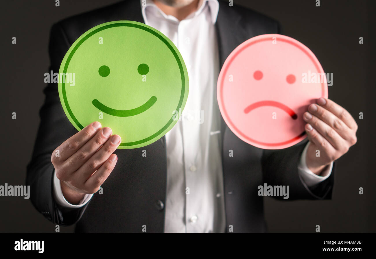 Business man with happy smiling and sad unhappy cardboard paper smiley face emoticon. Rating and giving review about - Stock Image
