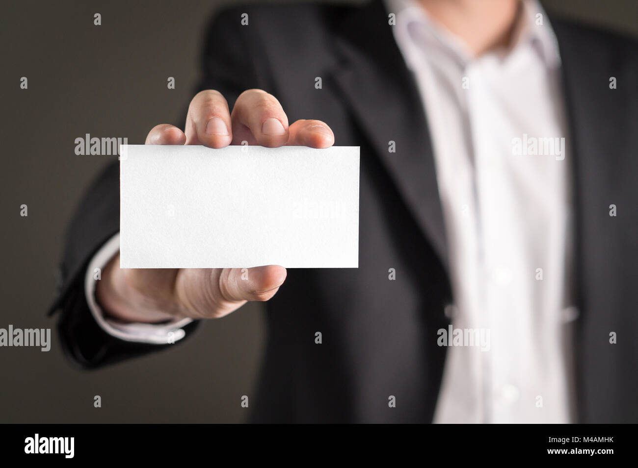Business man holding empty white business card. - Stock Image