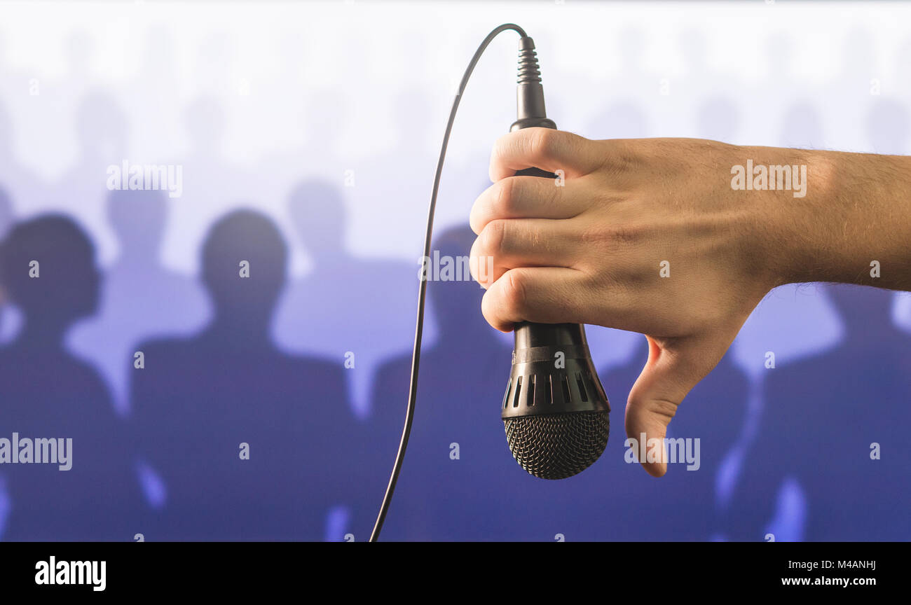 Hand holding microphone and showing thumbs down in front of a crowd of silhouette people. Failed public speaking - Stock Image