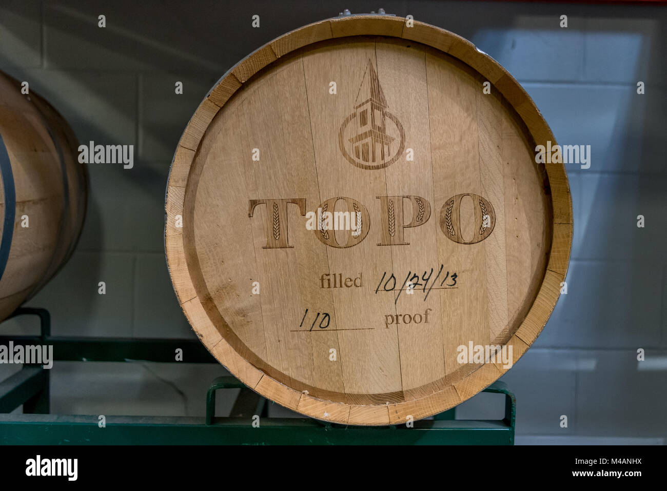 An aging wooden barrel of spirits at Topo Organic Spirits Distillery in Chapel Hill, North Carolina. - Stock Image