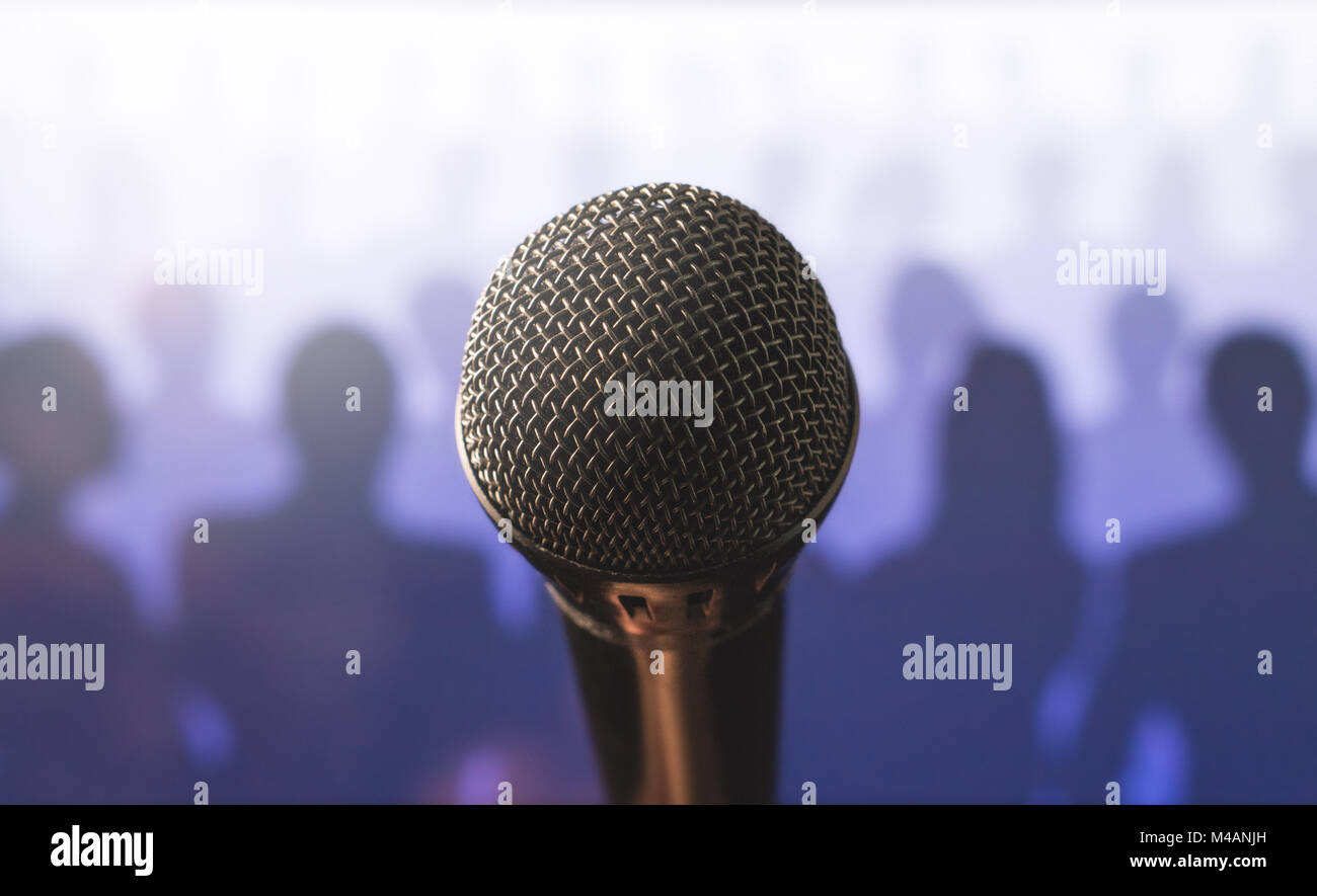 Close up of microphone in front of a silhouette audience and crowd of people. Public speaking and giving speech. - Stock Image