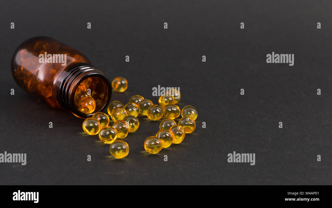 Spilled yellow transparent golden capsules of vitamine on dark background as skin treatment concept Stock Photo