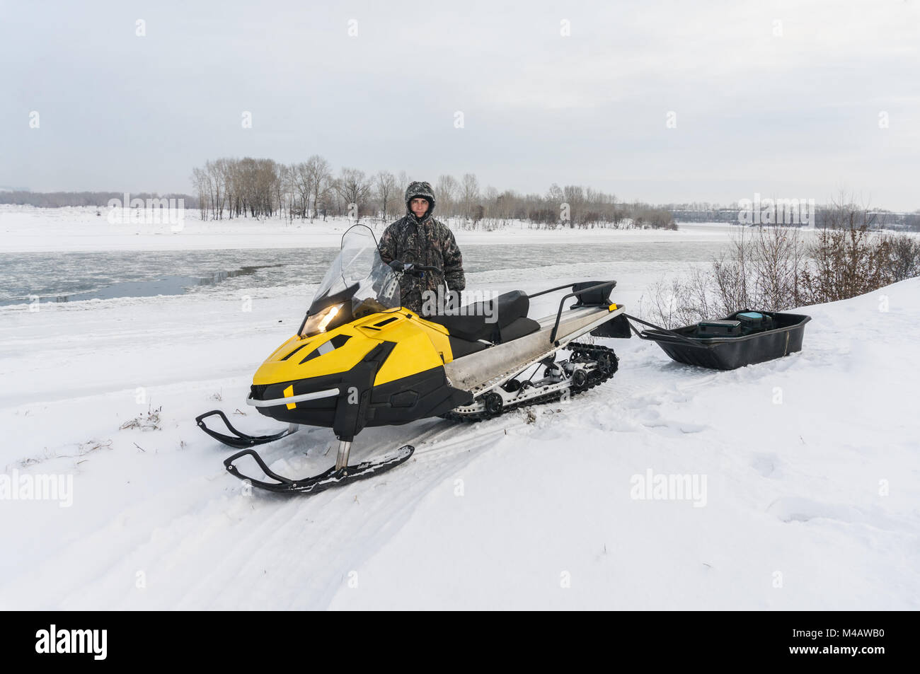 Fisherman on a snowmobile - Stock Image