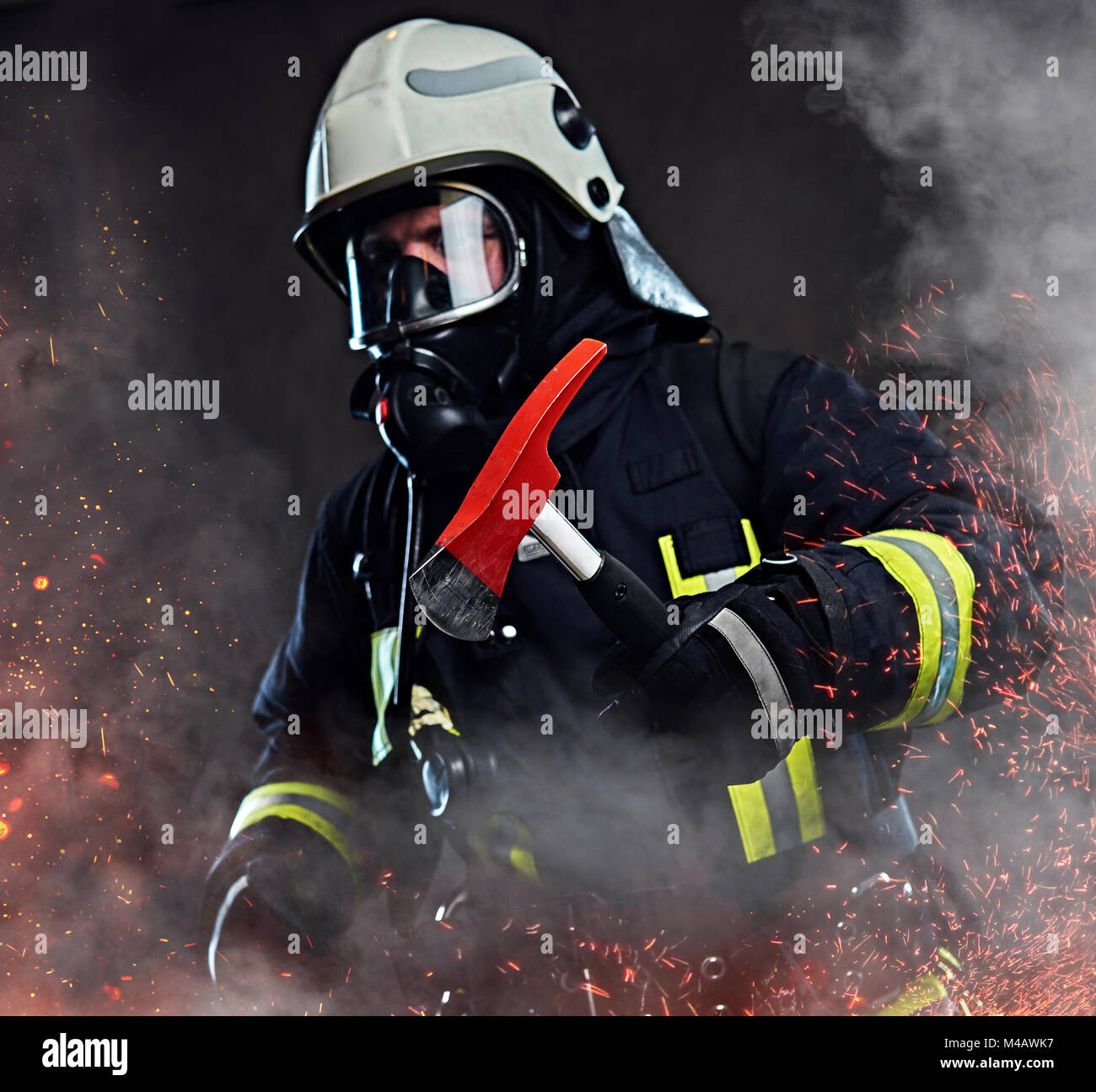 A firefighter dressed in a uniform in a studio. - Stock Image