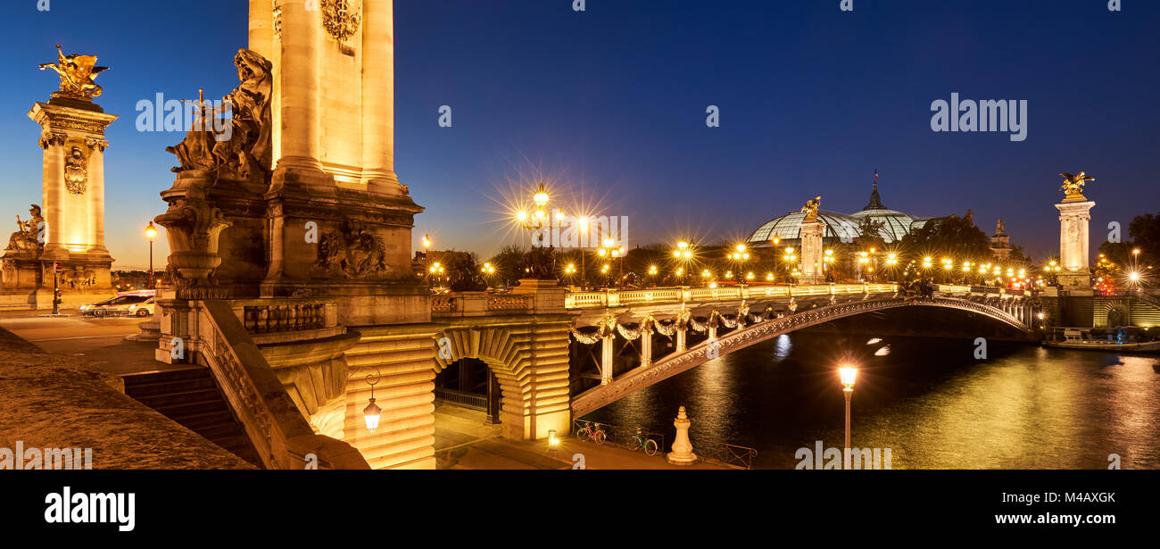 Panoramic view of the Pont Alexandre III Bridge illuminated at night with Seine River. 8th Arrondissement, Paris, - Stock Image